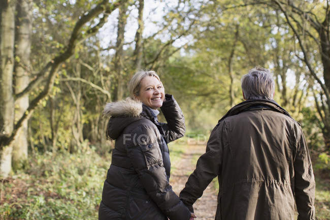 Mature caucasian couple walking together in autumn park — Stock Photo