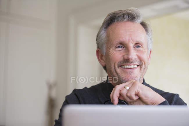 Lächelnder, selbstbewusster Freiberufler, der am Laptop arbeitet — Stockfoto