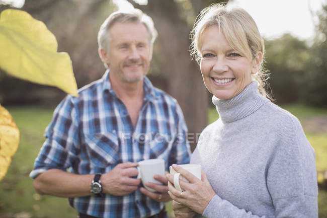 Couple Mature mature caucasian couple drinking coffee in garden — casual clothing