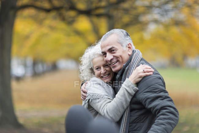 Felice coppia anziana che si abbraccia nel parco autunnale — Foto stock