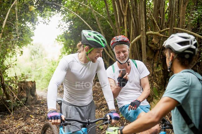 Male friends mountain biking, using smart phone in woods — Stock Photo