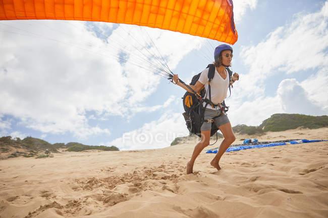 Parapendio maschile corsa con paracadute sulla spiaggia — Foto stock