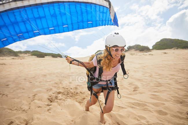 Sorrindo feminino parapente executando com para-quedas na praia — Fotografia de Stock