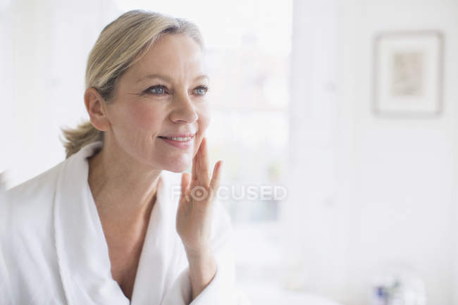 Smiling mature woman applying moisturizer to face at bathroom mirror — Stock Photo
