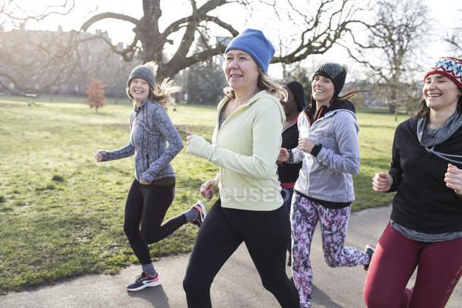Smiling female runners running in sunny park — Stock Photo