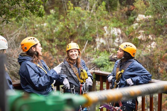 Smiling women friends talking, waiting to zip line — Stock Photo