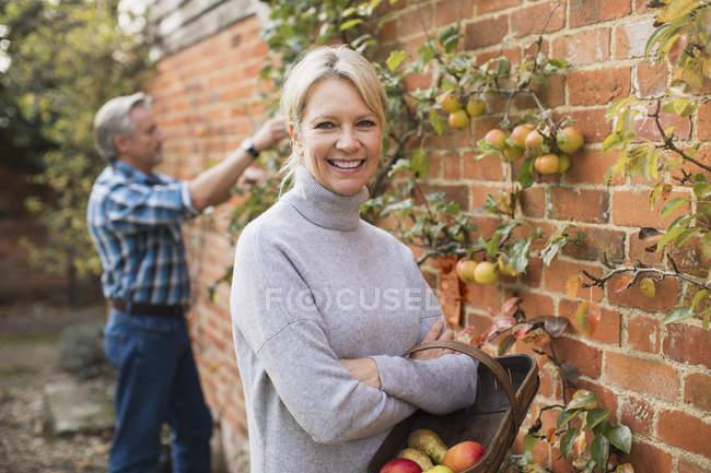 Mature couple caucasien cueillette de fruits dans domestique dans jardin — Photo de stock