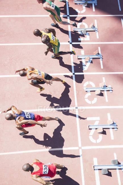 Спринтеры взлетают с стартовых блоков на трассе — стоковое фото