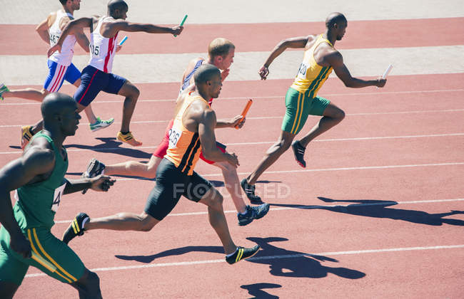 Relay runners racing on track — Stock Photo