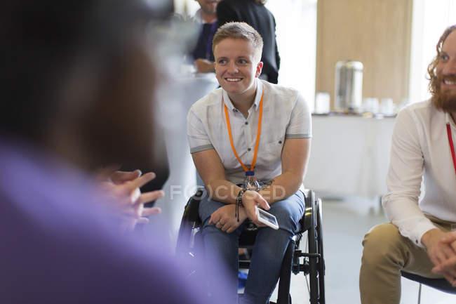 Femme souriante en fauteuil roulant parlant à des collègues en conférence — Photo de stock