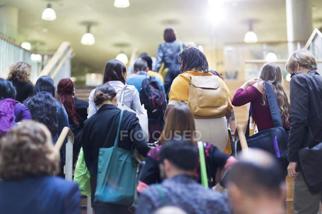 Folle di persone con zaini e borse che salgono le scale — Foto stock