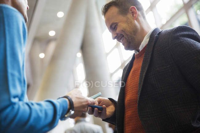 Businessman texting with smart phone at modern office — Stock Photo
