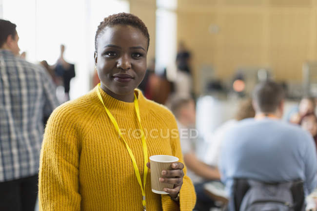 Portrait confident businesswoman drinking coffee at conference — Stock Photo