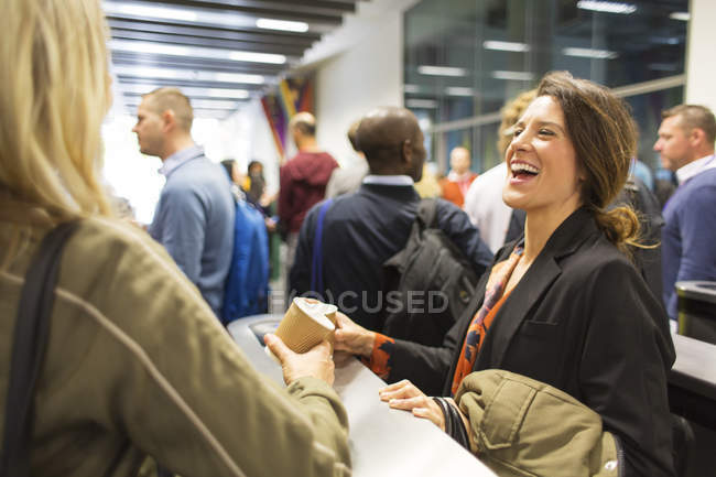 Laughing businesswomen drinking coffee at conference — Stock Photo
