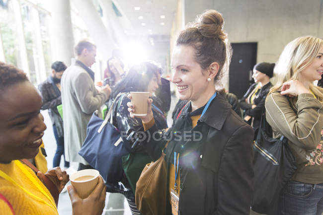 Smiling businesswomen talking and drinking coffee at conference — Stock Photo