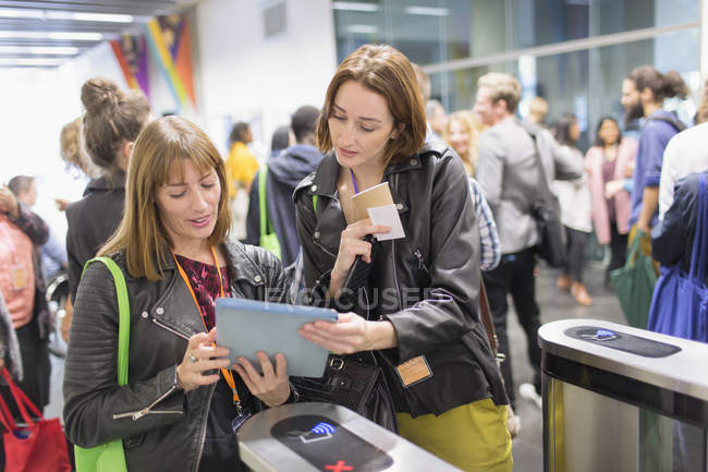 Women with digital tablet at turnstile at modern office — Stock Photo