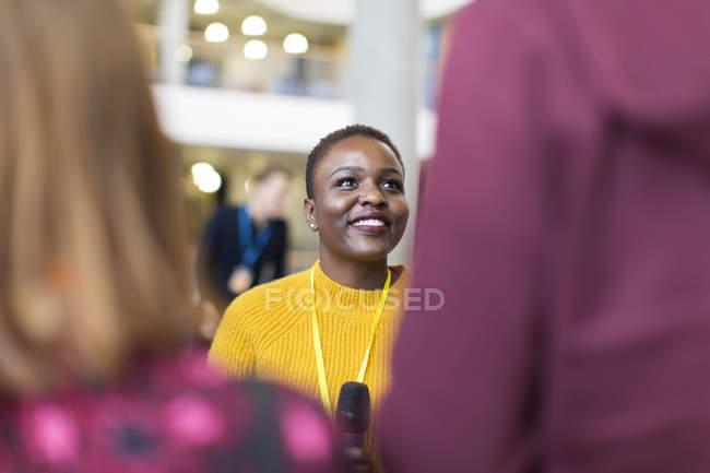 Récitante souriant parlant au public au bureau moderne — Photo de stock