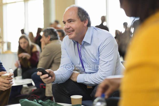 Empresário sorrindo usando telefone inteligente na conferência — Fotografia de Stock