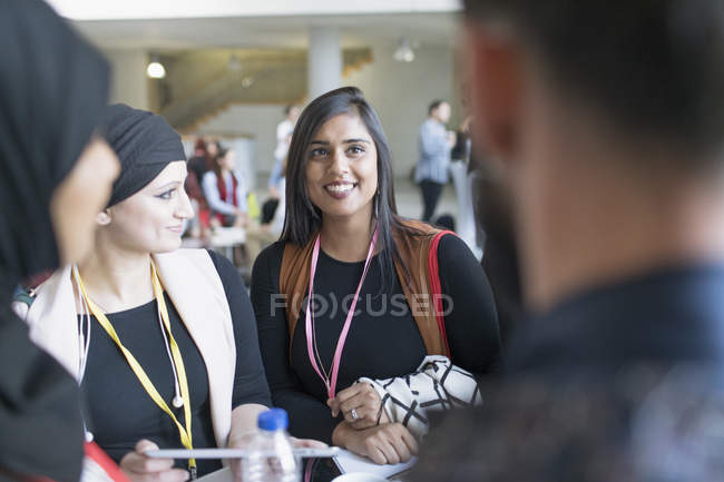 Des femmes d'affaires souriantes parlent à la conférence — Photo de stock