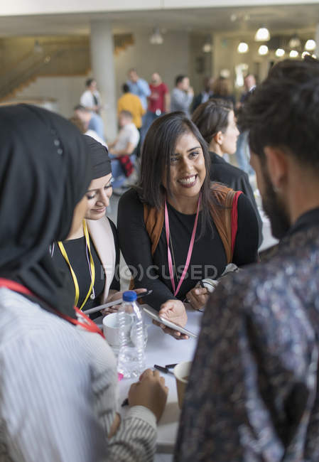 Smiling business people using smart phone at conference — Stock Photo