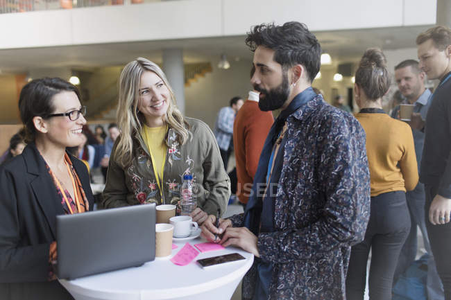 Business people talking, using laptop at conference — Stock Photo