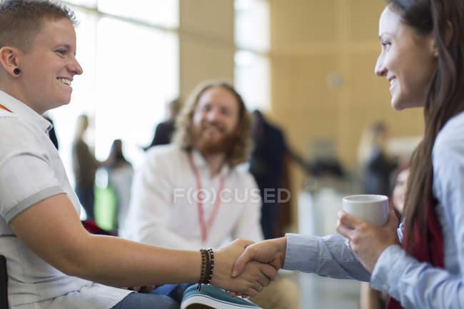 Бізнес-леді рукостискань на конференції в сучасному офісі — стокове фото