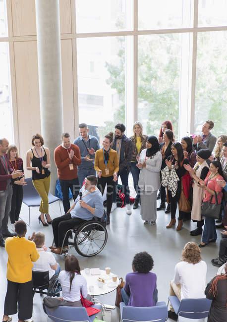 Audiência aplaudindo para orador masculino em cadeira de rodas — Fotografia de Stock
