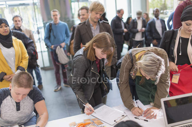 Business people arriving, checking in at conference registration table — Stock Photo