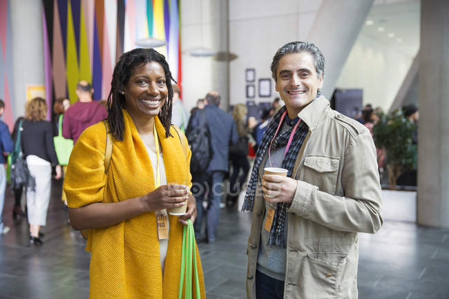Portrait smiling, confident businessman and businesswoman drinking coffee at conference — Stock Photo
