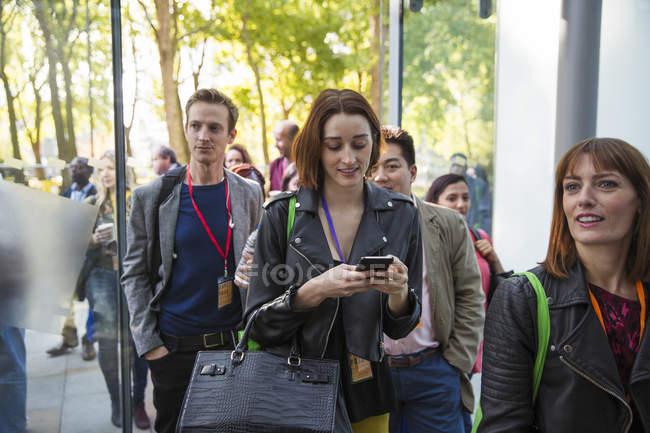 Businesswoman with smart phone arriving, entering doorway — Stock Photo