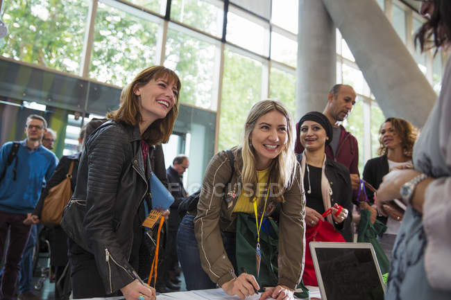 Arrivano donne d'affari sorridenti, al tavolo delle iscrizioni alle conferenze — Foto stock