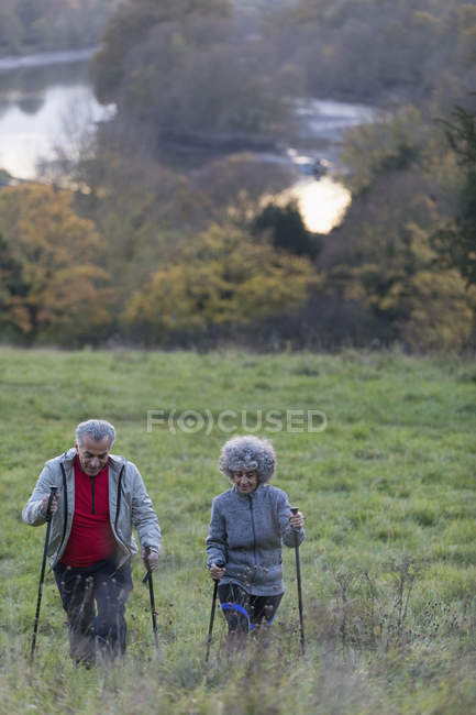Active senior couple hiking up rural hillside — Stock Photo