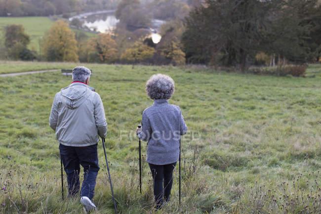 Aktive Senioren paar Wandern mit Stöcken im ländlichen Bereich — Stockfoto