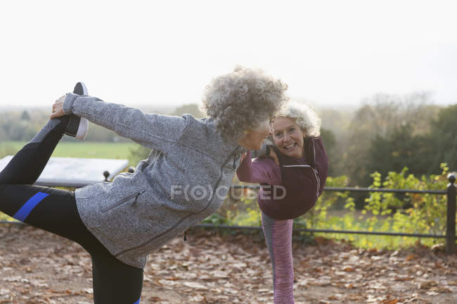 Active senior women friends stretching, practicing yoga in autumn park — Stock Photo
