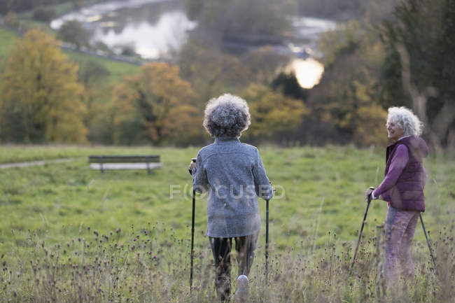 Active senior women friends hiking with poles in rural field — Stock Photo