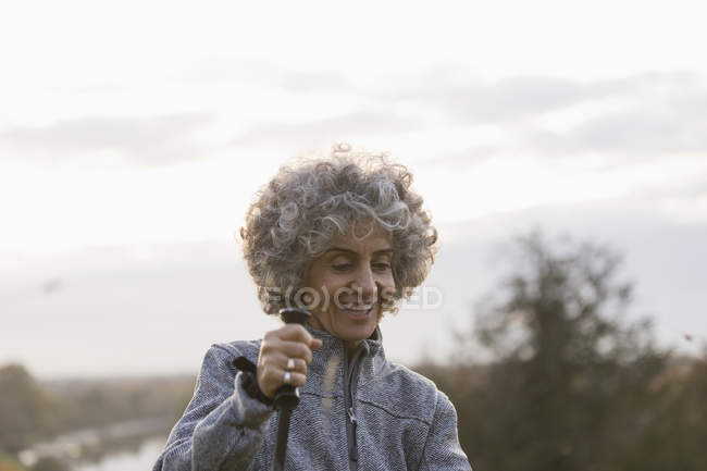 Smiling active senior woman hiking with pole — Stock Photo
