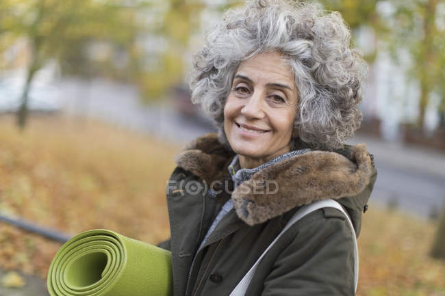 Portrait smiling, confident active senior woman with yoga mat — Stock Photo