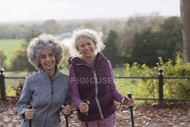 Portrait smiling, confident active senior women friends hiking with poles — Stock Photo