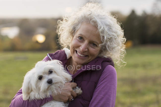 Портрет улыбается, счастливая активная пожилая женщина держит собаку — стоковое фото