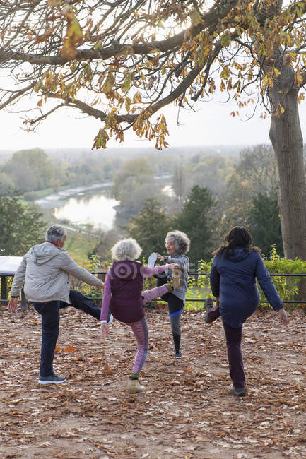 Active seniors stretching, exercising in autumn park — Stock Photo