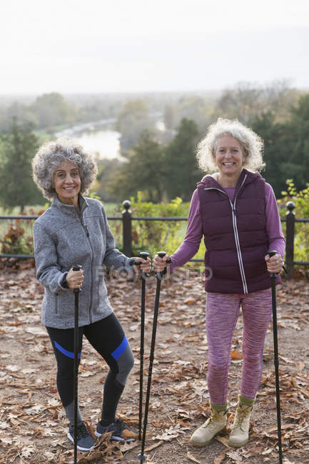 Portrait smiling, confident active senior women friends hiking with poles in autumn park — Stock Photo