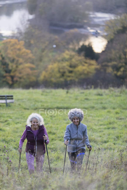 Active senior women friends hiking with poles up rural hillside — Stock Photo