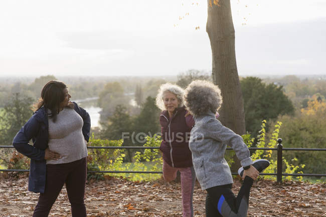 Active senior women friends stretching legs, preparing for run in autumn park — Stock Photo