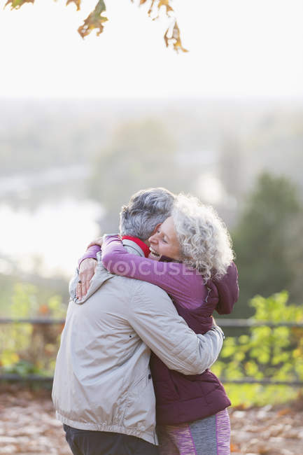 Affectionate active senior couple hugging in park — Stock Photo