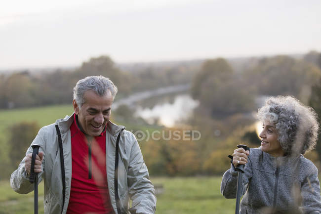 Active senior couple hiking with poles in park — Stock Photo