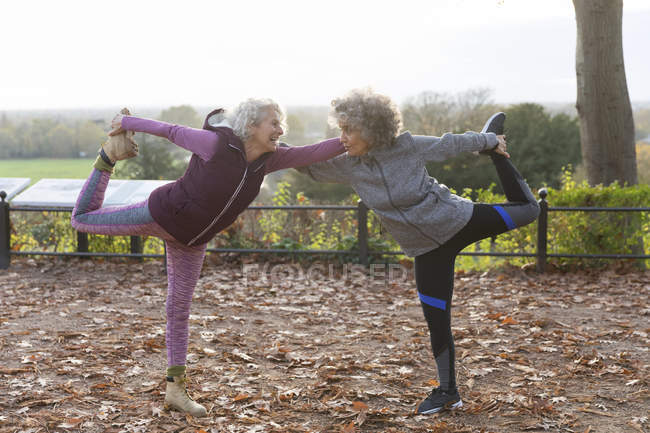 Active senior women friends stretching in autumn park — Stock Photo