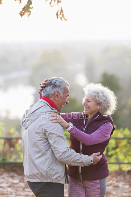 Sorridente, affettuosa coppia anziana attiva che si abbraccia nel parco autunnale — Foto stock