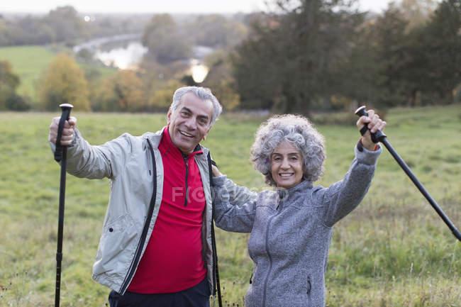 Porträt begeistert, überzeugt aktive senior paar Wandern mit Stöcken im ländlichen Bereich — Stockfoto