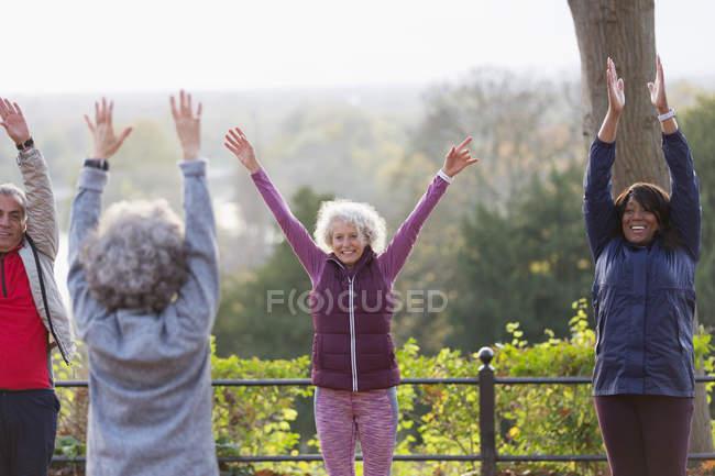 Aînés et énergiques et confiants, pratiquer l'yoga dans le parc — Photo de stock