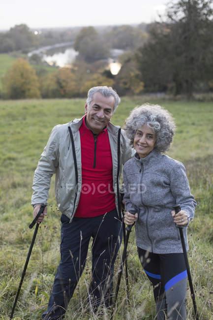 Ritratto fiducioso attivo coppia anziana escursioni con pali in campo rurale — Foto stock